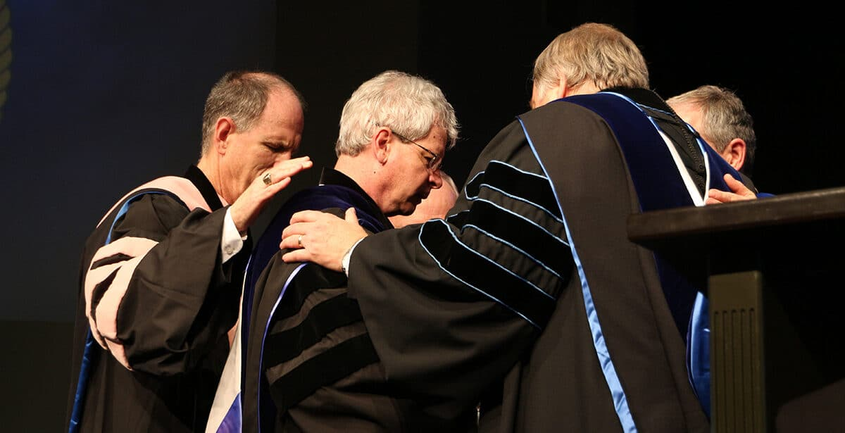 graduates praying together
